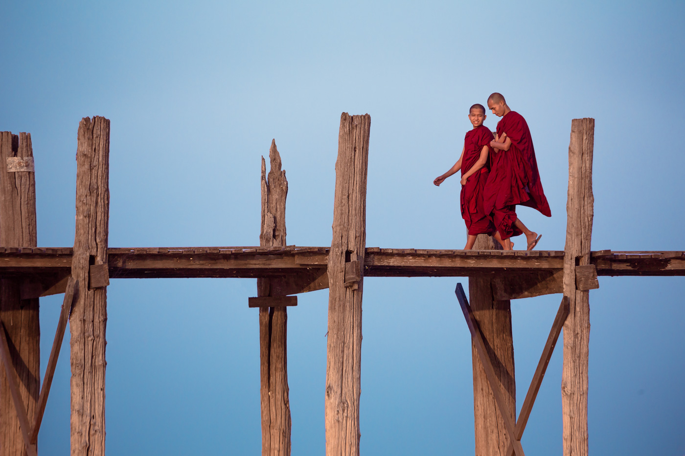 Monks on footbridge. Myanmar
